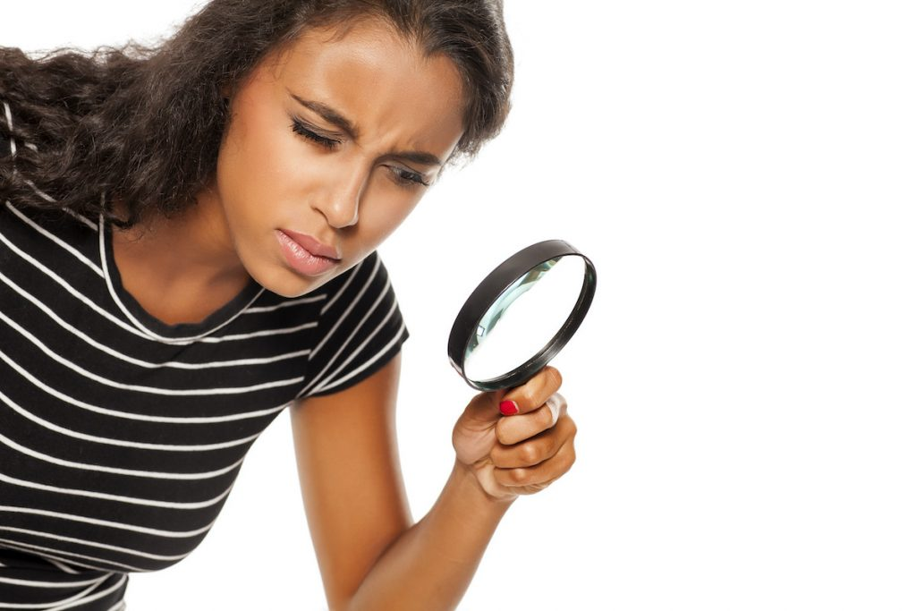 A woman holding a magnifying glass, looking like an emotion detective