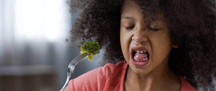Girl reluctantly eating brocoli
