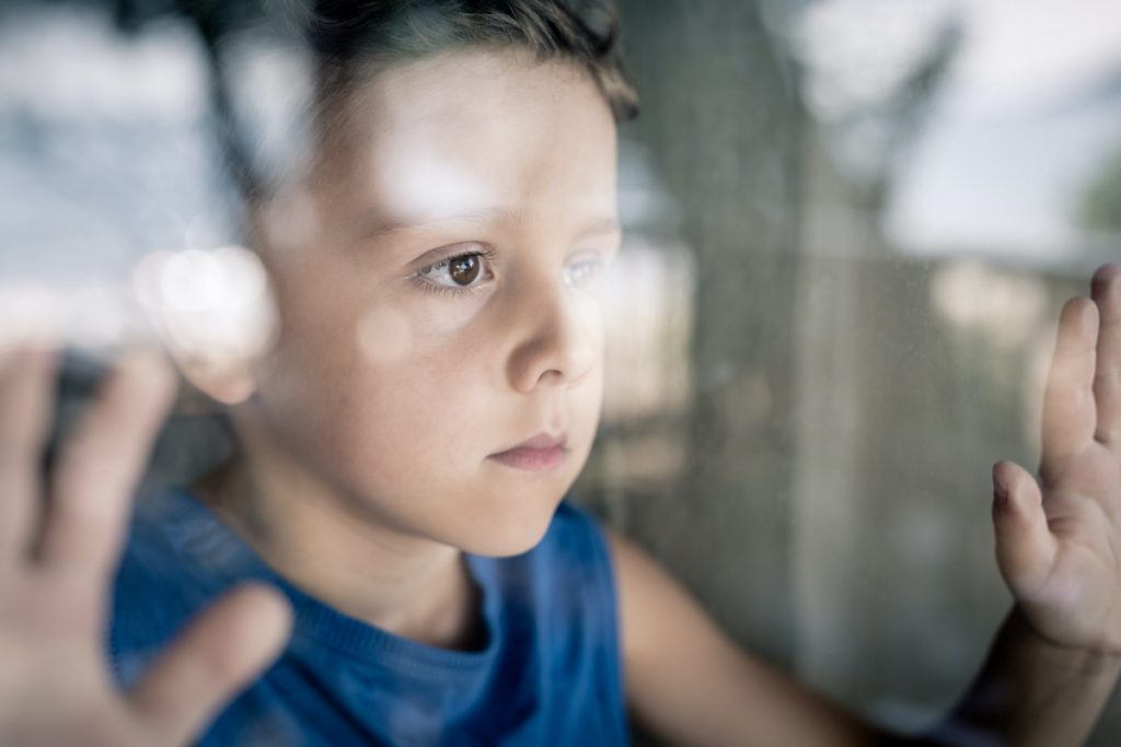 A sad child; article: how to help your child avoid depression