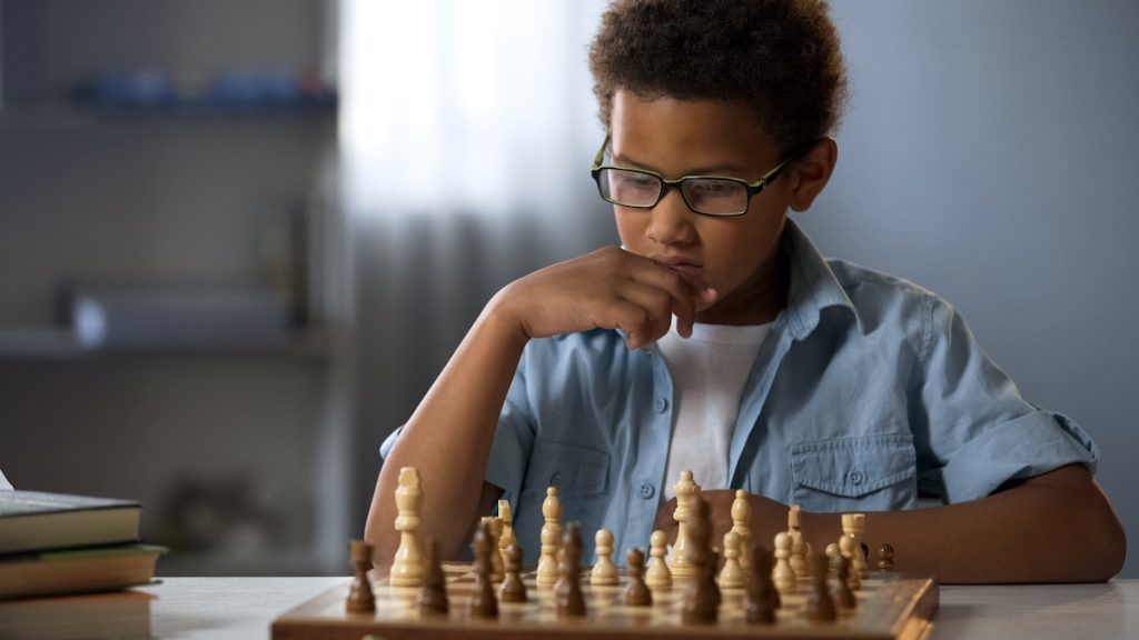 [photo of boy engrossed in playing chess; well-being comes in part from engagement]