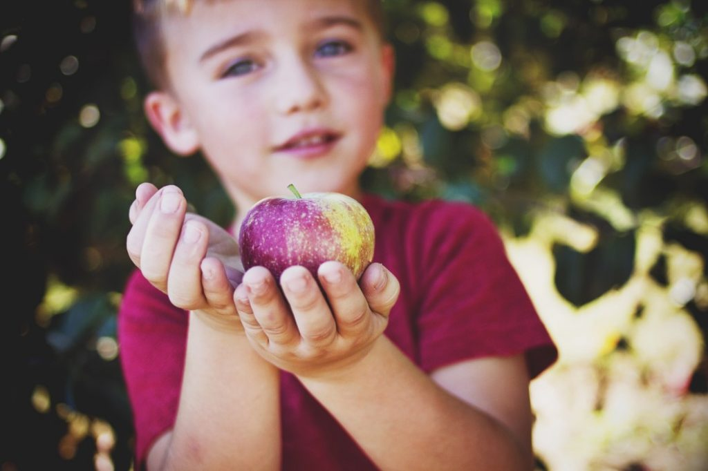 {Photo: child holding apple]