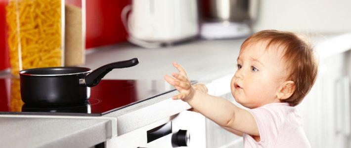 [photo: child reaching toward hot stove]