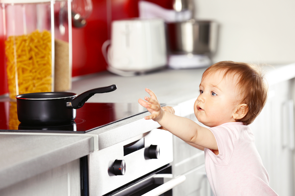 [photo: child reaching toward hot stove]